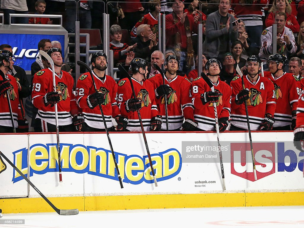 Members of the Chicago Blackhawks tap their sticks against the wall as an announcement is made that coach Joel Quenneville had picked up his 685th win, putting him 4th on the all-time NHL coaches win talley, during a game against the Vancouver Canucks at the United Center on December 20, 2013 in Chicago, Illinois.