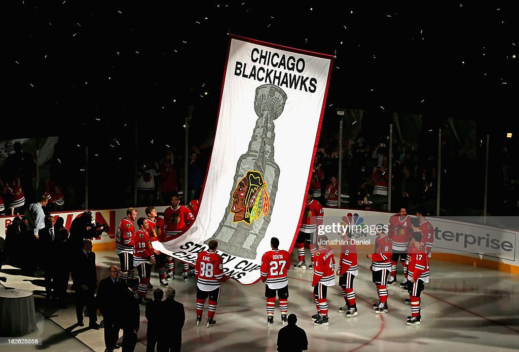 Members of the Chicago Blackhawks watch as the 2013 Stanley Cup Championship banner is hung during a ceremony before taking on the Washington Capitals at the United Center on October 1, 2013 in Chicago, Illinois.