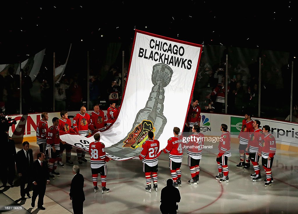 Members of the Chicago Blackhawks watch as the 2013 Stanley Cup Championship banner is hung during a ceremony before taking on the Washington Capitals at the United Center on October 1, 2013 in Chicago, Illinois. The Blackhawks defeated the Capitals 6-4.