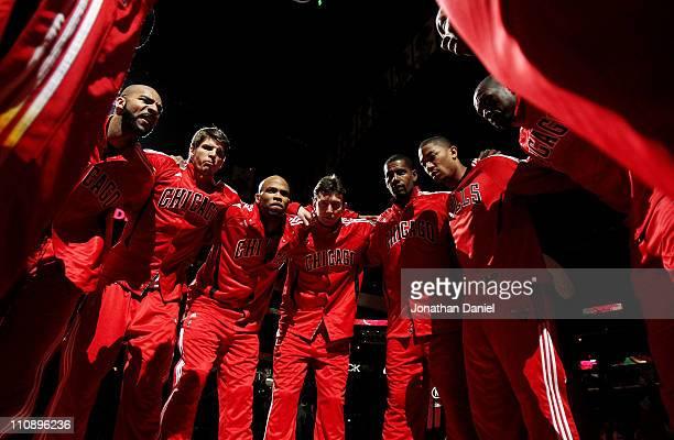 Members of the Chicago Bulls including Carlos Boozer Kyle Korver Taj Gibson Omer Asik Kurt Thomas Derrick Rose Loul Deng and Keith Bogans huddle...