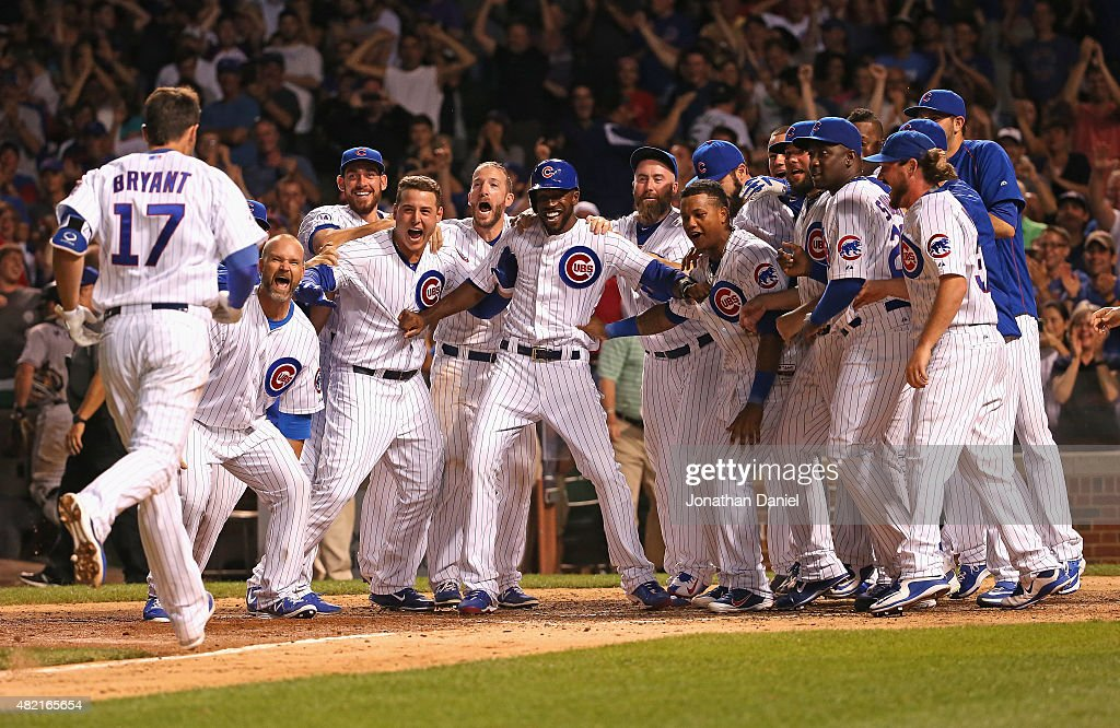 Members of the Chicago Cubs wait to welcome Kris Bryant #17 after he hit a game-winning, two-run home run in the bottom of the 9th inning against the Colorado Rockies at Wrigley Field on July 27, 2015 in Chicago, Illinois. The Cubs defeated the Rockies 9-8.