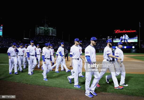 Members of the Chicago Cubs walk back to the dugout after raising the 2016 World series Champions banner before the home opening game against the Los...