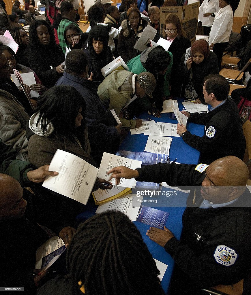 Members of the Chicago Police Department pass out information on how to apply for a job to job seekers during the City of Chicago job fair at Kennedy King College in Chicago, Illinois, U.S., on Friday, Nov. 9, 2012. The U.S. Department of Labor is scheduled to release initial jobless claims data on Nov. 15. Photographer: Frank Polich/Bloomberg via Getty Images