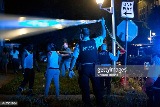 Members of the Chicago Police Department put up tape and clear the scene of a fatal shooting in the 700 block of North Ridgeway Avenue Sunday June 26...