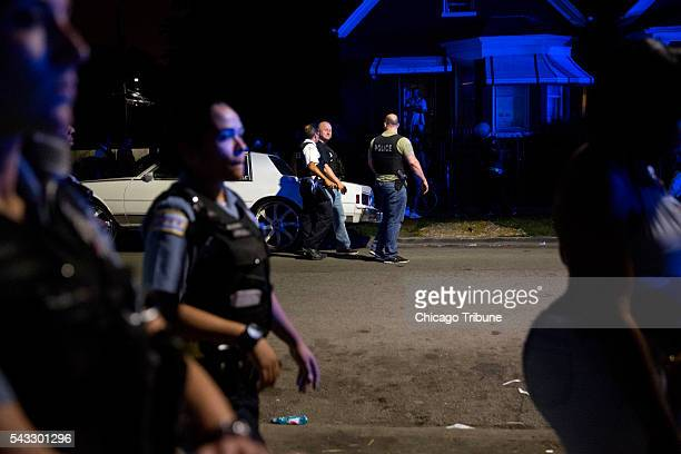Members of the Chicago Police Department walk down the street as they clear the scene of a fatal shooting in the 700 block of North Ridgeway Avenue...