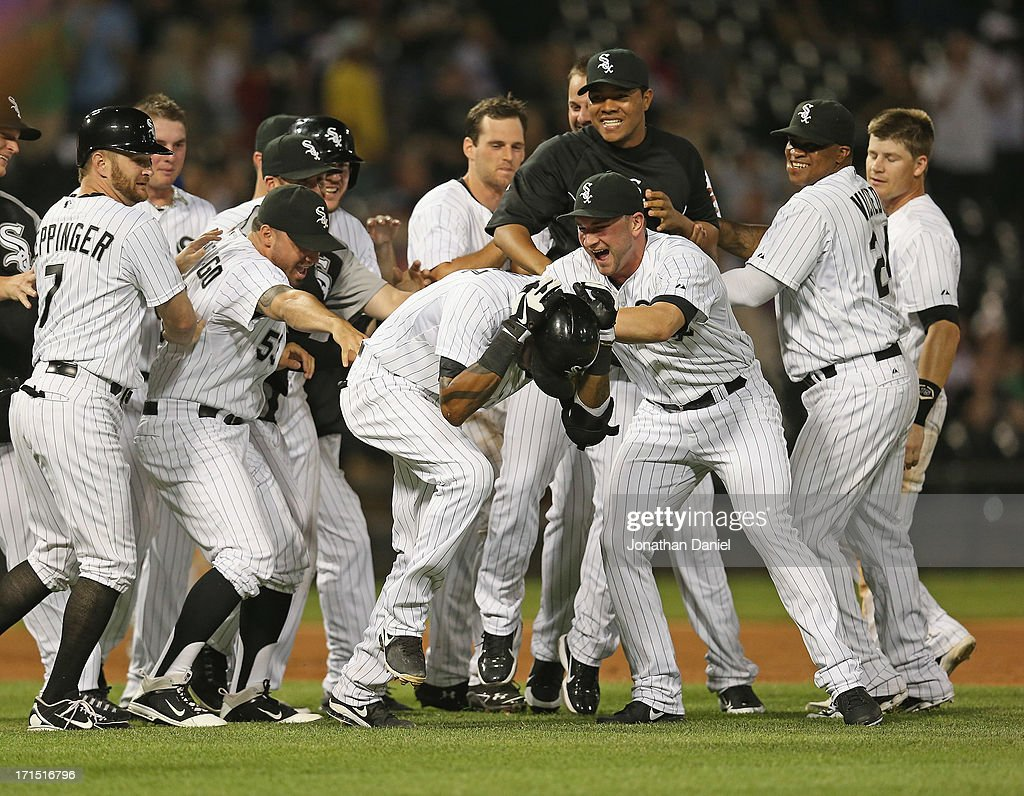 Members of the Chicago White Sox mob teammate <a gi-track='captionPersonalityLinkClicked' href=/galleries/search?phrase=Alexei+Ramirez&family=editorial&specificpeople=690568 ng-click='$event.stopPropagation()'>Alexei Ramirez</a> #10 (center, head down) after he got the game-winning hit in the bottom of the 9th inning against the New York Mets at U.S. Cellular Field on June 25, 2013 in Chicago, Illinois. The White Sox defeated the Mets 5-4.