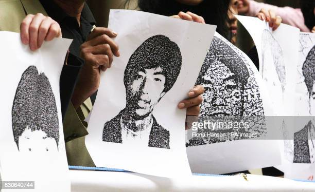 Members of the Chinese Civil Rights Action Group holding images of the 58 Chinese illegal immigrants commemorate the 54 men and four women who...