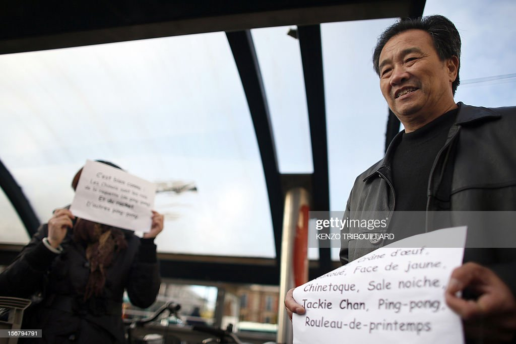 Members of the Chinese community in France hold placards during a demonstration against xenophobia called by the association 'Francais de Chine, Chinois de France' (French from China, Chinese of France) on November 21, 2012 near the French newspaper Le Parisien's headquarters in Saint-Ouen, a northern suburb of Paris. Demonstrators denounce the stereotypes their community is subjected to after Le Parisien published on November 11 a special issue on the Chinese mafia in France. AFP PHOTO / KENZO TRIBOUILLARD