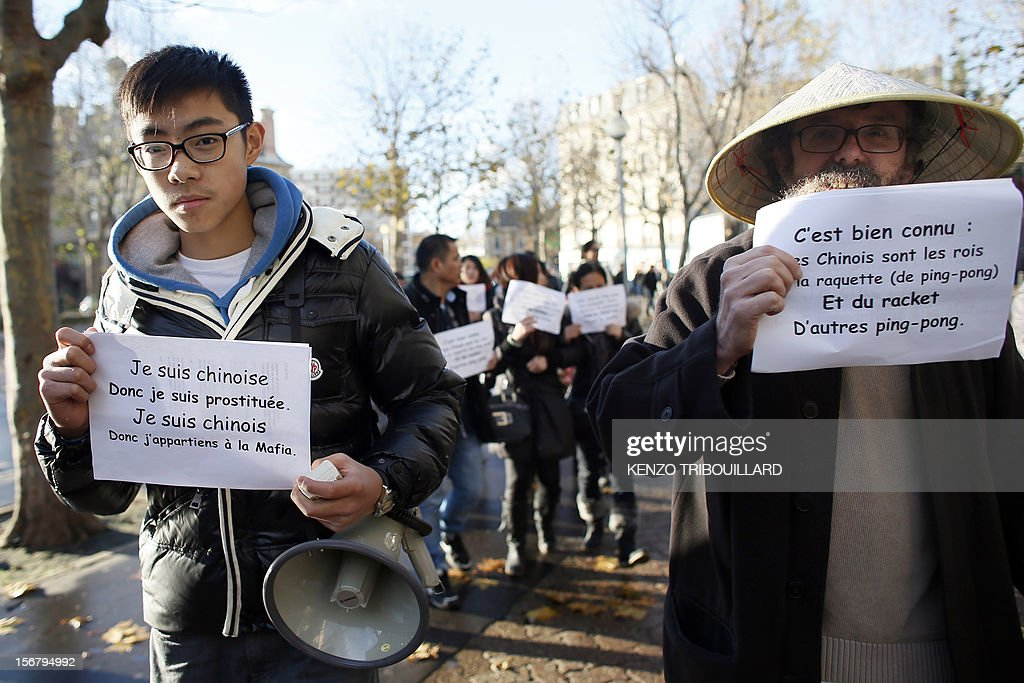 Members of the Chinese community in France hold posters during a demonstration against xenophobia called by the association 'Francais de Chine, Chinois de France' (French from China, Chinese of France) on November 21, 2012 near the French newspaper Le Parisien's headquarters in Saint-Ouen, a northern suburb of Paris. Demonstrators denounce the stereotypes their community is subjected to after Le Parisien published on November 11 a special issue on the Chinese mafia in France. AFP PHOTO / KENZO TRIBOUILLARD