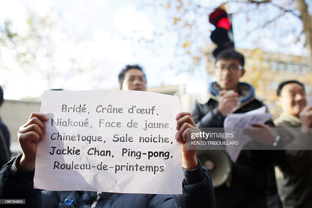 Members of the Chinese community in France hold posters with derogatory mentions and insults during a demonstration against xenophobia called by the association 'Francais de Chine, Chinois de France' (French from China, Chinese of France) on November 21, 2012 near the French newspaper Le Parisien's headquarters in Saint-Ouen, a northern suburb of Paris. Demonstrators denounce the stereotypes their community is subjected to after Le Parisien published on November 11 a special issue on the Chinese mafia in France. AFP PHOTO / KENZO TRIBOUILLARD