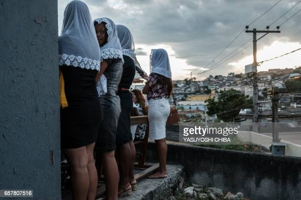 Members of the Christian Congregation in Brazil sing a hymn outside of their overcrowded church at Complexo do Alemao community in Rio de Janeiro...