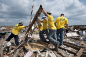 Members of the Church Of Jesus Christ Of Latter Day Saints of Independence Kansas attempt to lift a stormdamaged wall while clearing the remains of a...