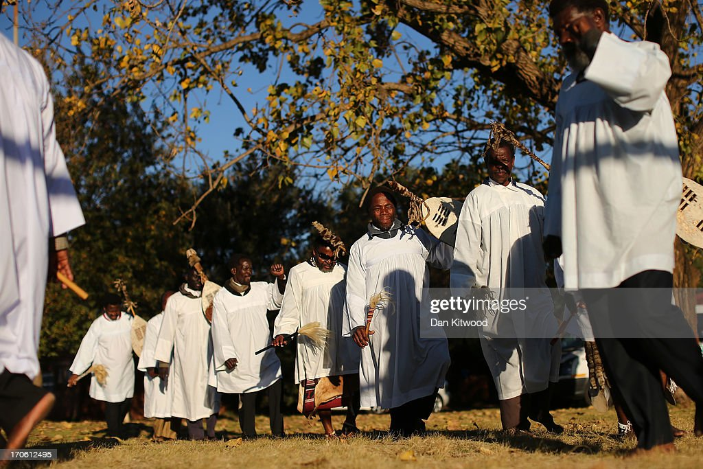 Members of the Church of Nazareth take part in a service at Rockville School, in Soweto on June 15, 2013 in Johannesburg, South Africa. The Baptist church, which is a mixture of Zulu tradition and Christianity, continued their daily life as the former South African President and leader of the anti-apartheid movement who is spending a seventh night in hospital. It has been reported that he is responding better to treatment for a recurring lung infection.