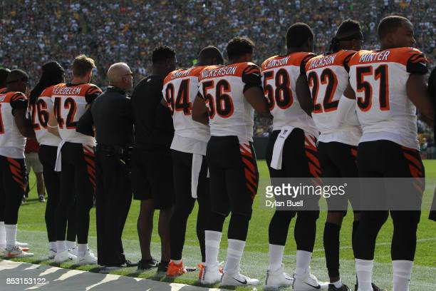 Members of the Cincinnati Bengals stand with arms locked as a sign of unity during the national anthem prior to their game against the Green Bay...
