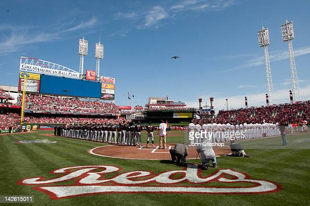 Members of the Cincinnati Reds and the Miami Marlins stand on the field during the National Anthem before their game on Thursday April 5 2012 at...