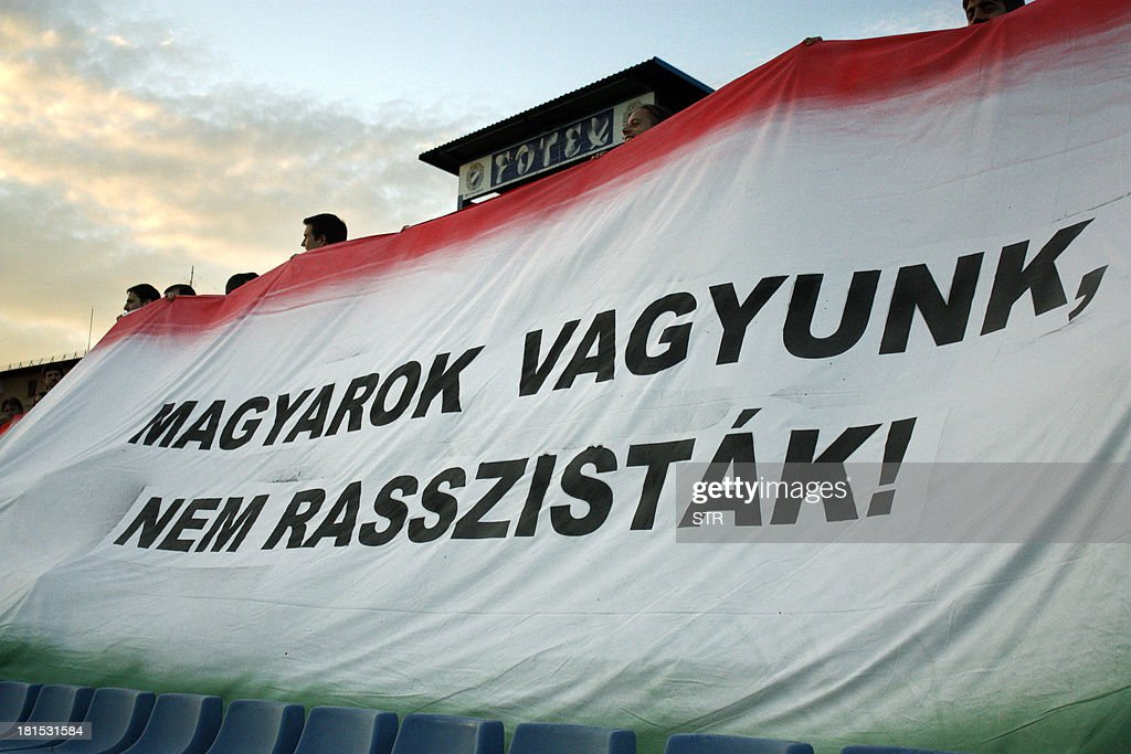 Members of the 'Civic platform', an independent organization of Hungarian football fans, spread a tricolor banner that reads 'We are Hungarians, not racist people' to stage a protest against hooligans during the Hungarian first league football match MTK vs Paks at the Hidegkuti stadium in Budapest, Hungary on September 21, 2013Hungarian football club Ferencvaros was fined thousands of euros by national sports authorities on Friday after fans commemorated the death of a suspected Nazi war criminal during a weekend match.