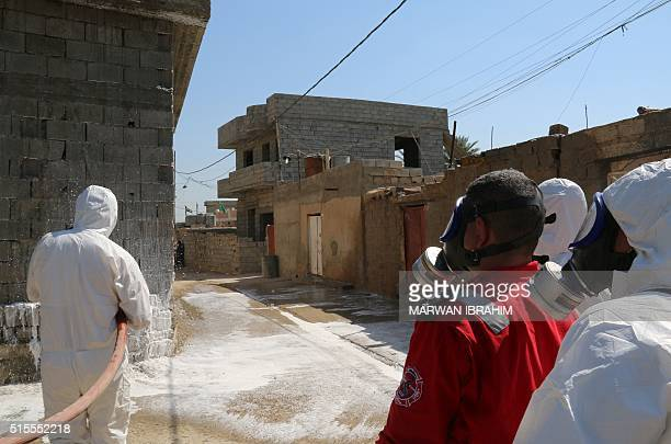 TOPSHOT Members of the civil defence spray and clean areas in the town of Taza around 220 kilometres north of the capital Baghdad on March 13 that...