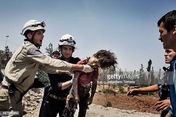 Members of the Civil Defense team remove the dead body of a 8 year old child from a destroyed car after being struck by a regime barrel bomb June 19...