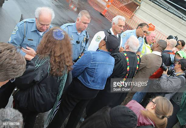 Members of the clergy pray for police officers during a protest outside the Ferguson police station on October 13 2014 in Ferguson Missouri Ferguson...