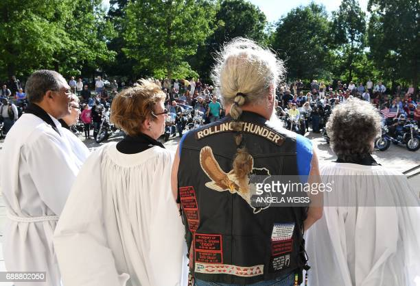 Members of the clergy speak to a crowd of motorcyclists during the 'Blessing of the Bikes' at the Washington National Cathedral May 26 2017 in...