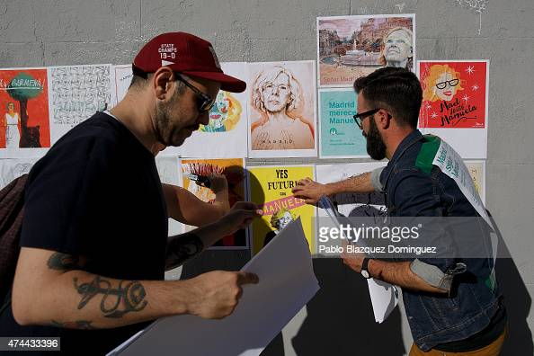 Members of the colective 'Madrid With Manuela' stick images depicting 'Ahora Madrid' candidate Manuela Carmena to support her on the last day of the...