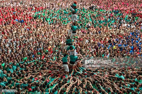 Members of the colla 'Castellers de Vilafranca' fall down as they built a human tower during the 26th Tarragona Competition on October 2 2016 in...