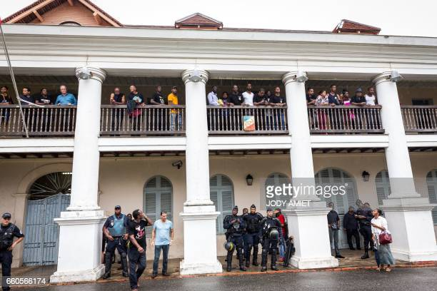 TOPSHOT Members of the collective '500 freres' and of the delegations stand on the balcony of the prefecture to inform the crowd gathered outside the...