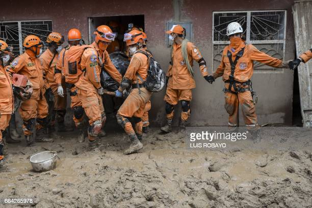 TOPSHOT Members of the Colombian civil defense remove the body of a woman who died in the mudslide caused by heavy rains in Mocoa Putumayo department...