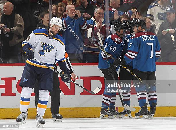 Members of the Colorado Avalanche celebrate a goal as Chris Butler the St Louis Blues looks on at the Pepsi Center on December 23 2014 in Denver...