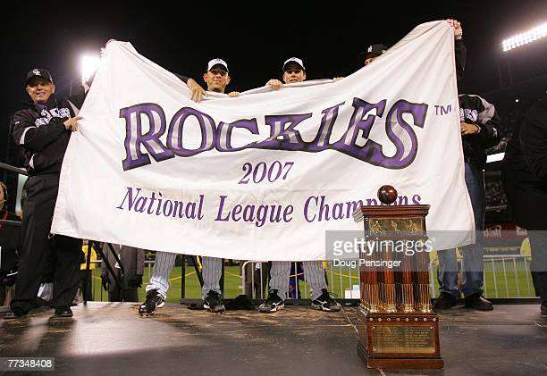 Members of the Colorado Rockies celebrate with a banner and the trophy after they won 64 against the Arizona Diamondbacks during Game Four of the...