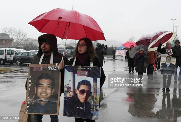 Members of the committee of victims carry pictures of relatives as they arrive at the trial of the rail disaster of Viareggio that killed 32 people...