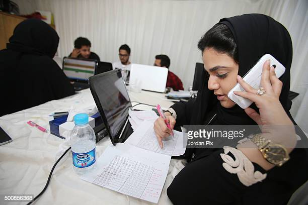 Members of the communication staff for the campagin of a female candiate for the upcoming Saudi municipal elections work hard on contacting and...