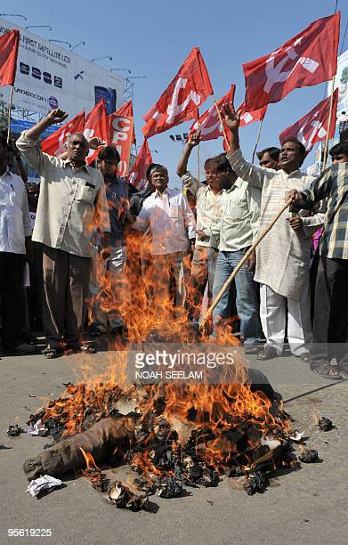 Members of the Communist Party India Marxist shout slogans and burn an effigy of the state government during their protest against busfare hikes in...
