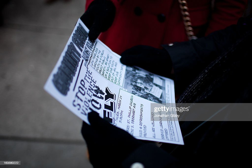 Members of the community read a flyer encouraging individuals to come forward with information regarding the killing of Jonylah Watkins on March 12, 2013 in Chicago, Illinois. The 6-month-old girl was shot five times on the 6500 block of South Maryland Avenue while her father was changing her diaper in the passenger seat of his car. The father, Jonathan Watkins remains is stable condition at Nothwestern Memorial Hospital after receiving three gunshot wounds.