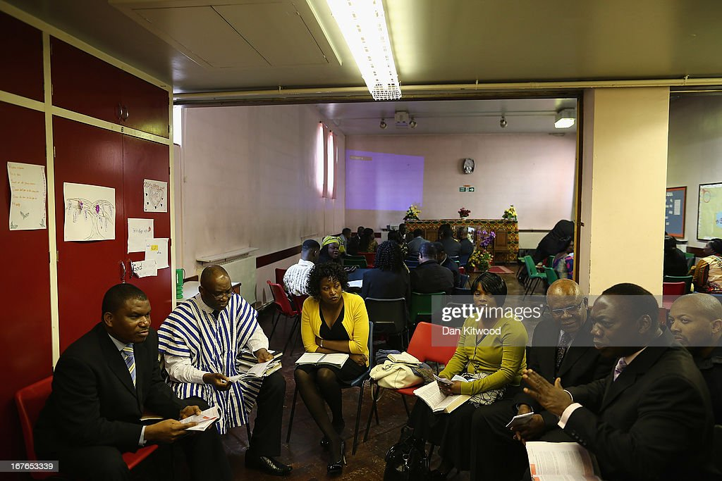 Members of the congregation discuss the Bible ahead of a 'Seventh Day Evangelist' service at Crossway Church in the Heygate Estate on April 27, 2013 in London, England. The Crossway Church is an international church, with the congregation made up of native Londoners as well as people from Ghana, Jamaica, South Africa, Zimbabwe, Korea, Brazil, Eastern Europe and the United States. It has been serving the local community at different sites around Elephant and Castle for almost 150 years. The church has been at it's current location in the Heygate estate since 1974. The Heygate estate in central London was built in 1974 as social housing and housed around 3000 people, but fell into a state of disrepair, gaining a reputation for crime and poverty. The estate is due to be demolished as part of the £1.5billion GBP 'Elephant & Castle regeneration scheme', and replaced with 2,500 'affordable' new homes. The area has become popular with street artists, storytellers, and guerilla gardeners and attracts an array of urban wildlife including bats, birds and mammals.