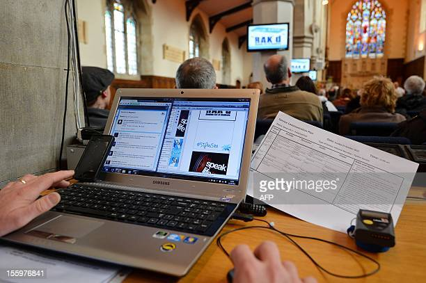 A members of the congregation uses a laptop computer to post message onto screens during a service held by Children's Church and Youth Pastor Brian...