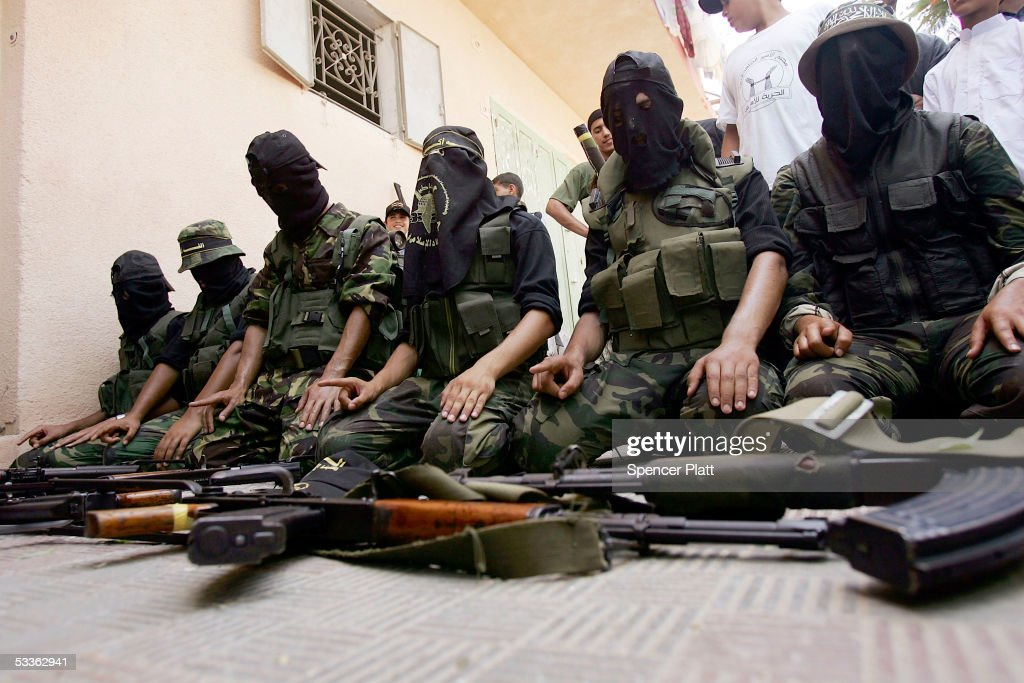 Members of the controversial Palestinian group Islamic Jihad display weapons while praying before walking through the streets in a march with...