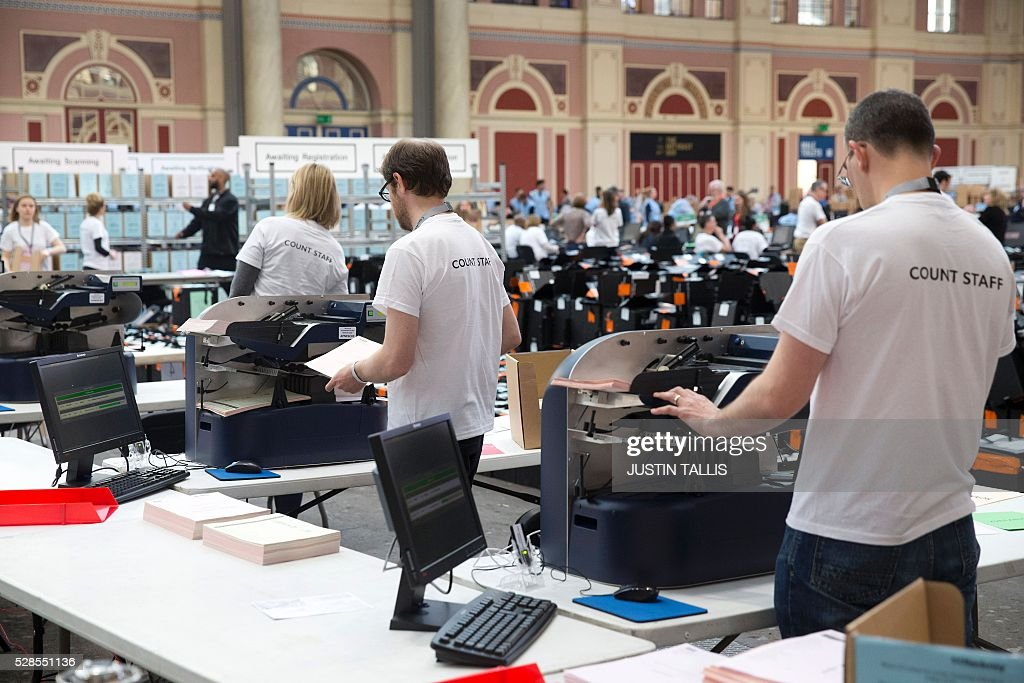 Members of the counting staff use electronic machines to count ballot papers at a count centre in north London on May 6, 2016. Early results Friday from British local and regional elections seen as a key test for opposition Labour leader Jeremy Corbyn showed strong gains for Scottish nationalists, as London looked set to elect its first Muslim mayor. London was on track to become the first EU capital with a Muslim mayor as voters went to the polls Thursday after a bitter campaign between Prime Minister David Cameron's Conservatives and the opposition Labour party. / AFP / JUSTIN