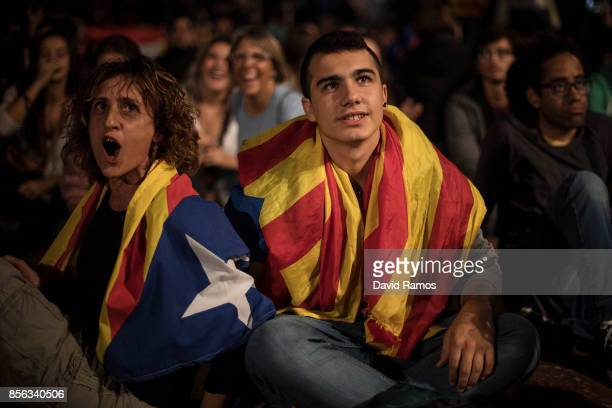 Members of the crowd draped in a Catalan Proindependence flag react as they watch a large screen showing the speech of the Spain's Prime Minister...