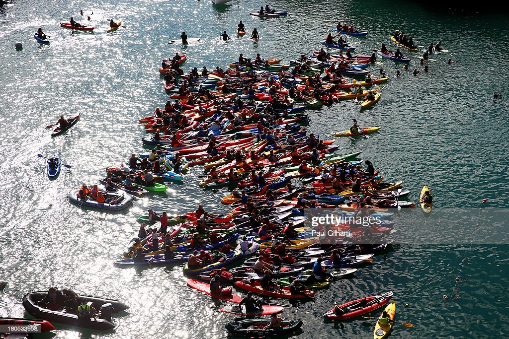 Members of the crowd gather on canoes, kayaks, and boats to watch the competitors dive during the Red Bull Cliff Diving World Series 2013 at Blue Lagoon on September 14, 2013 in Abereiddy, Wales. Competitors dive from a platform 27 metres above the sea and enter the water at 85-90kph during the two-day international competition.
