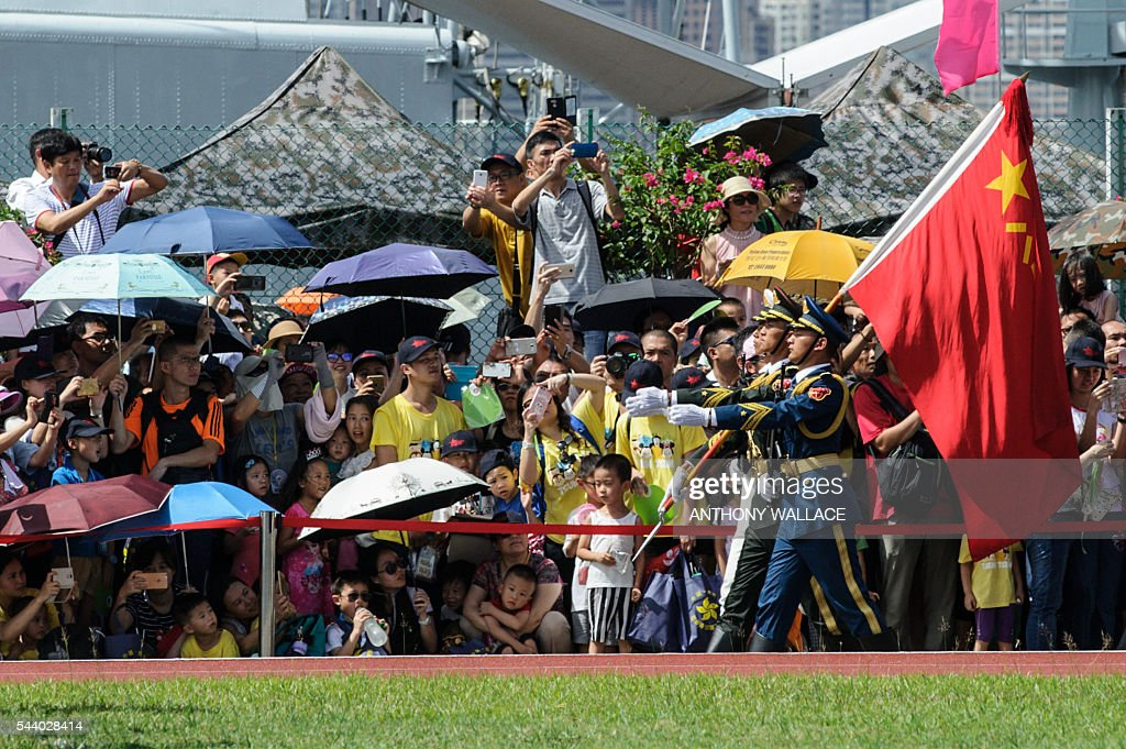 Members of the crowd react as PLA soldiers march with the Chinese flag during the open day of the Chinese People's Liberation Army (PLA) Navy Base at Stonecutter Island in Hong Kong on July 1, 2016, to mark the 19th anniversary of the Hong Kong handover to China. / AFP / Anthony Wallace