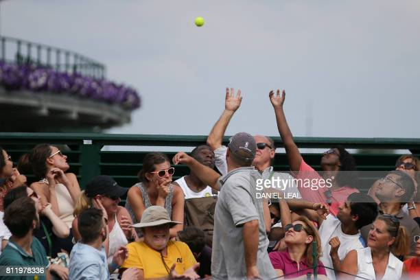 Members of the crowd try to catch a stray ball as South Africa's Kevin Anderson plays against US player Sam Querrey during their men's singles fourth...