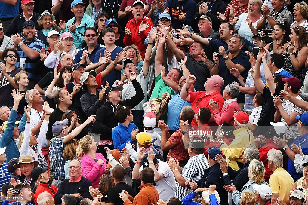 Members of the crowd try to catch the ball of Rory McIlroy of Northern Ireland as he throws it into the crowd following his two-stroke victory on the 18th green during the final round of The 143rd Open Championship at Royal Liverpool on July 20, 2014 in Hoylake, England.