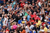 Members of the crowd try to catch the ball of Rory McIlroy of Northern Ireland as he throws it into the crowd following his twostroke victory on the...