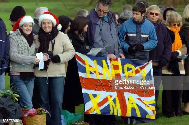 Members of the crowds hold a banner wishing Camilla The Duchess of Cornwall a Happy Christmas outside the Christmas day service at St Mary Magdalene...