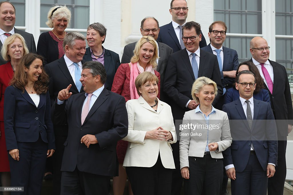 Members of the current German government, including German Chancellor Angela Merkel (C, in white), arrive to pose for a group photo during a break while meeting at Schloss Meseberg palace on May 24, 2016 near Gransee, Germany. The government cabinet is meeting at Schloss Meseberg for a two-day retreat to principally discuss Germany's digital future.