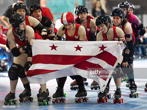 Members of the DC Rollergirls skate with a Washington DC flag as they are introduced to the crowd as they prepare to take on the Rideau Valley Vixens...