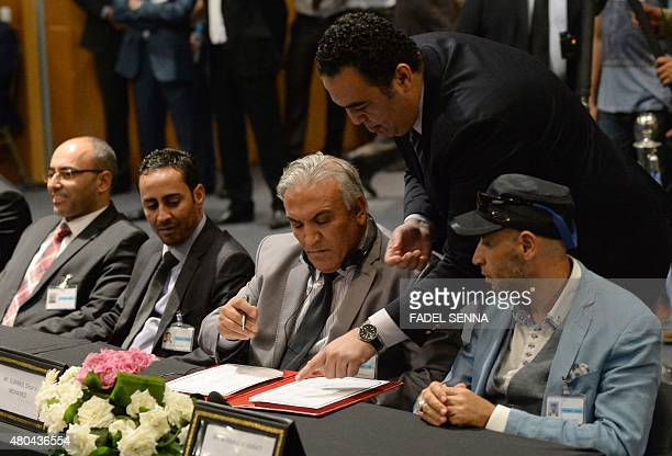 Members of the delegation from the government in the eastern city of Tobruk sign the document on a new version of a UNbrokered peace deal during the...