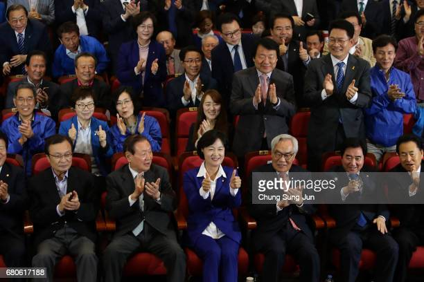 Members of the Democratic Party of Korea react as they watch a television report on an exit poll of the new president at the party's auditorium in...