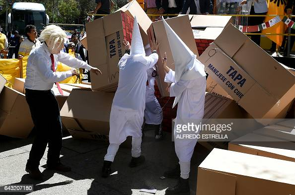 Members of the Democratic Revolution Party wearing a mask of US President Donald Trump and dressed as Ku Klux Klan members tear down a symbolic wall...